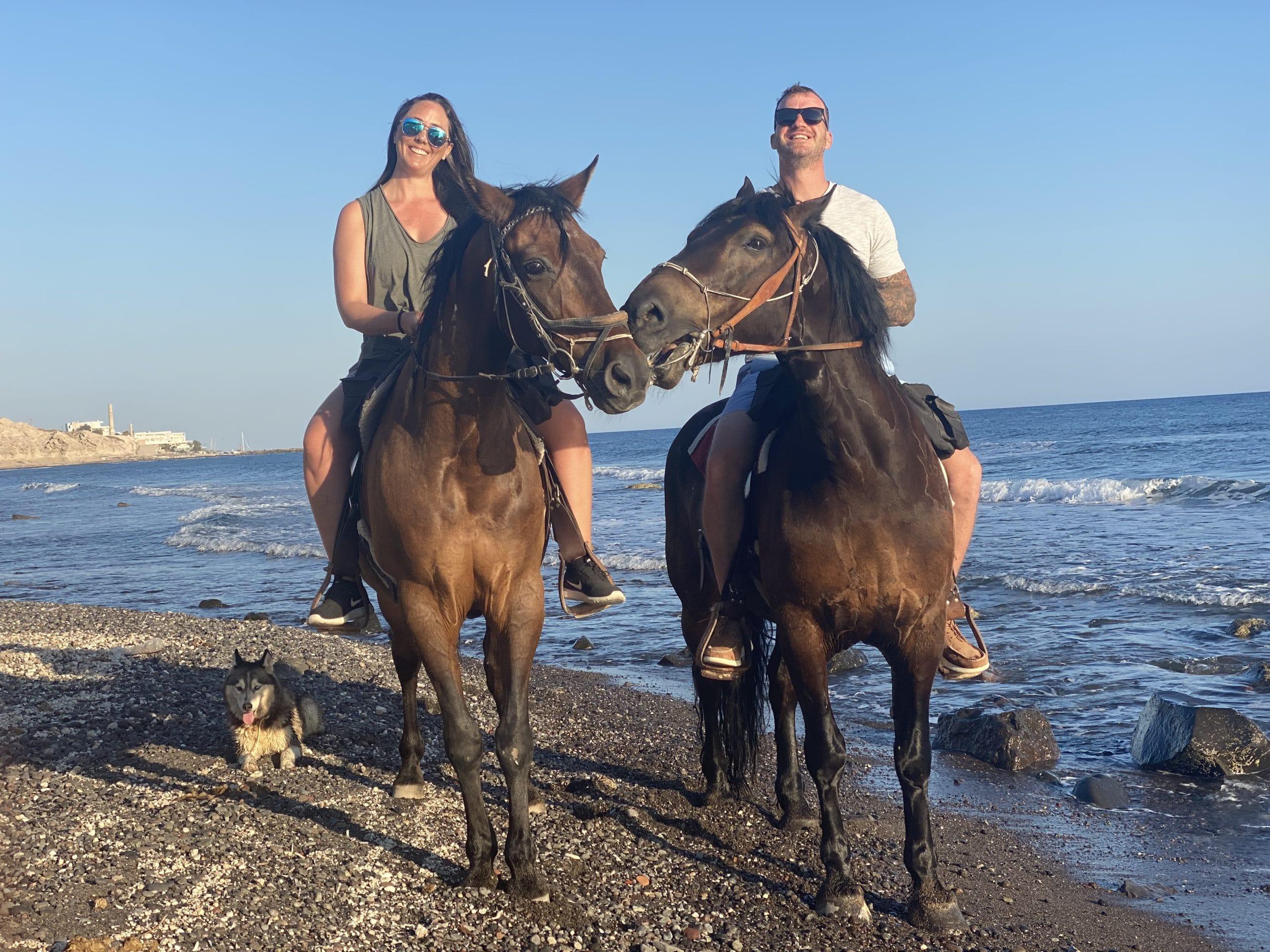 eric and lexy riding horses on the beach in santorini